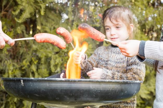 Groupe de personnes rôtir des saucisses sur un barbecue en plein air