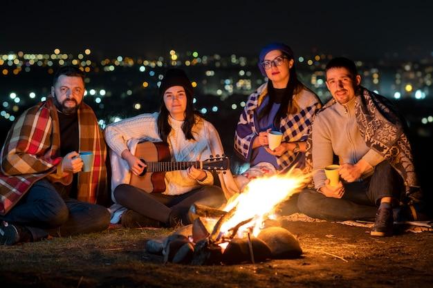 Groupe de personnes s'amusant assis près d'un feu de camp à l'extérieur la nuit à jouer de la guitare, à chanter des chansons et à parler joyeusement ensemble.