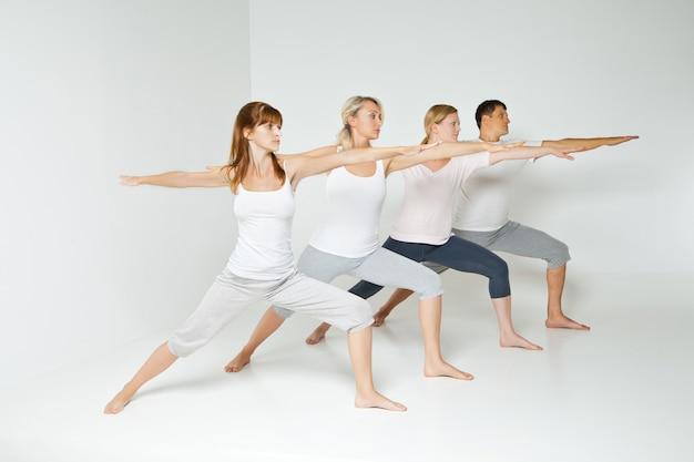 Groupe de personnes se relaxant et faisant du yoga en blanc