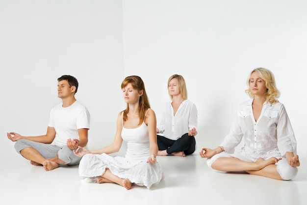 Groupe de personnes se relaxant et faisant du yoga en studio blanc