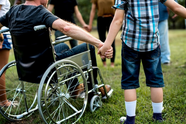 Groupe de personnes se tenant la main ensemble dans le parc