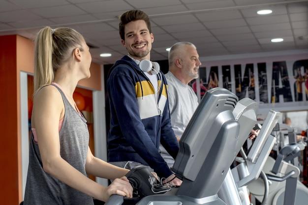 Groupe de personnes souriantes faisant de l'exercice ensemble sur des tapis roulants dans la salle de sport
