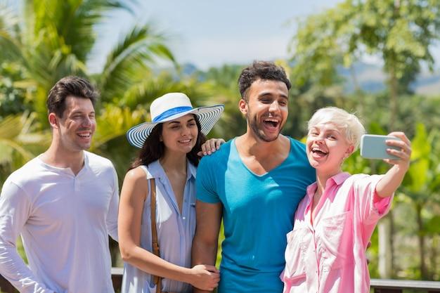 Groupe de personnes souriantes faisant selfie photo portrait enthousiaste mix race hommes et femmes