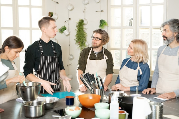Groupe de personnes en tablier regardant un entraîneur de cuisine masculin et l'écoutant pendant la classe de maître tout en se tenant autour d'une grande table de cuisine