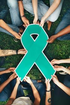 Groupe de personnes tenant un ruban de couleur verte