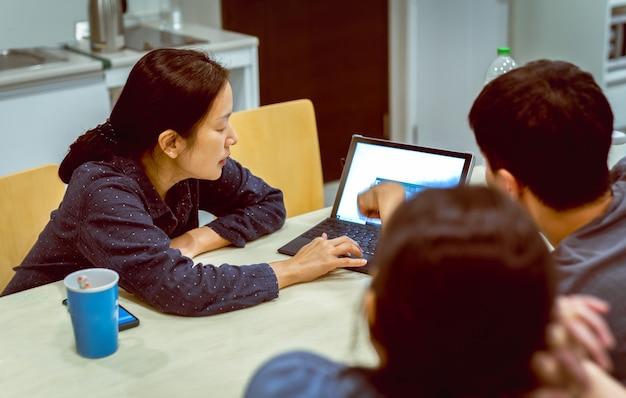 Groupe de personnes travaillant en équipe sur un ordinateur portable tard dans la nuit