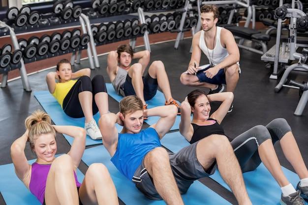 Groupe de personnes travaillant leurs abdominaux dans un gymnase