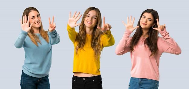 Groupe de personnes avec des vêtements colorés comptant sept avec les doigts sur fond coloré