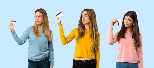 Groupe de personnes avec des vêtements colorés prenant une carte de crédit sans argent sur fond coloré