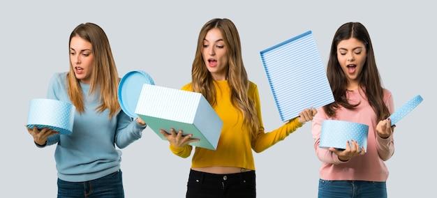 Groupe de personnes avec des vêtements colorés, tenant une boîte-cadeau dans les mains sur un fond coloré