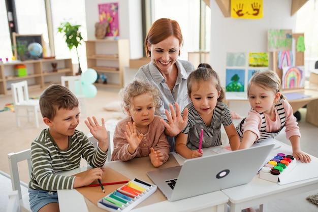 Un groupe de petits enfants de maternelle avec un enseignant à l'intérieur en classe, utilisant un ordinateur portable.