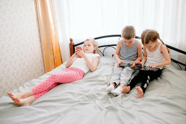 Groupe de petits enfants utilisant des smartphones ensemble