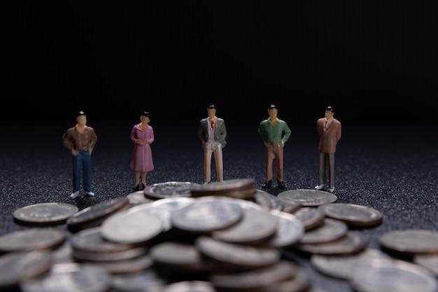 Groupe de petits entrepreneurs debout sur des pièces de monnaie
