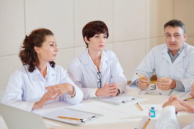 Groupe de pharmacologues sérieux parlant lors d'une réunion quotidienne et discutant des échantillons de vaccin covid 19