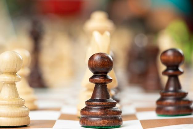Groupe de pièces d'échecs sur le plateau portable. jouer dans le concept de parc. repos en famille ou loisirs entre amis. activité de plein air.