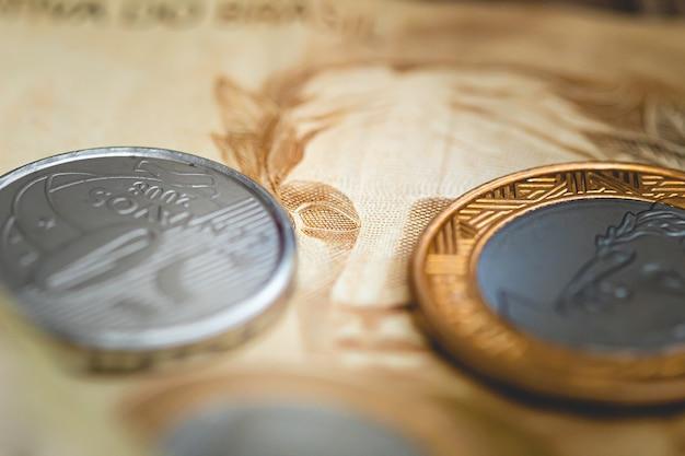 Un groupe de pièces de monnaie brésiliennes sur un vrai billet de banque brésilien pour le concept de l'économie brésilienne