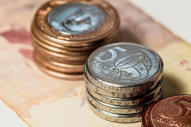 Un groupe de pièces de monnaie brésiliennes sur de vrais billets de banque brésiliens pour le concept de l'économie brésilienne