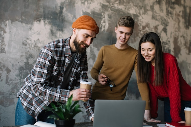 Groupe de pigistes travaillant ensemble à l'aide d'un ordinateur portable au bureau