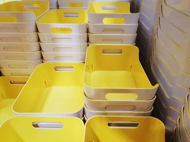 Groupe de piles de bacs en plastique jaune dans un magasin de vente au détail