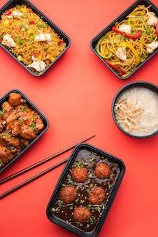 Groupe de plats indo-chinois livrés à domicile dans des emballages en plastique, des conteneurs ou des boîtes contenant des nouilles schezwan, du riz frit, du poulet au piment, de la manchourie et de la soupe.