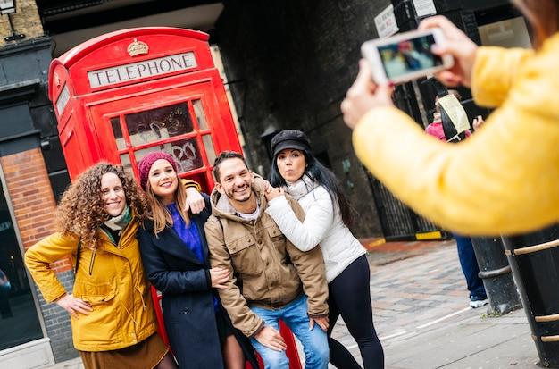 Un groupe de plusieurs amis prendre une photo dans une cabine téléphonique rouge sur une rue de londres