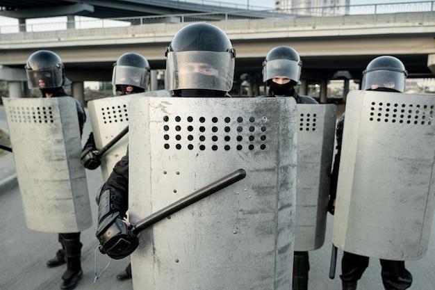 Groupe de policiers anti-émeute portant des casques frappant des boucliers avec des matraques tout en repoussant des manifestants dans la rue