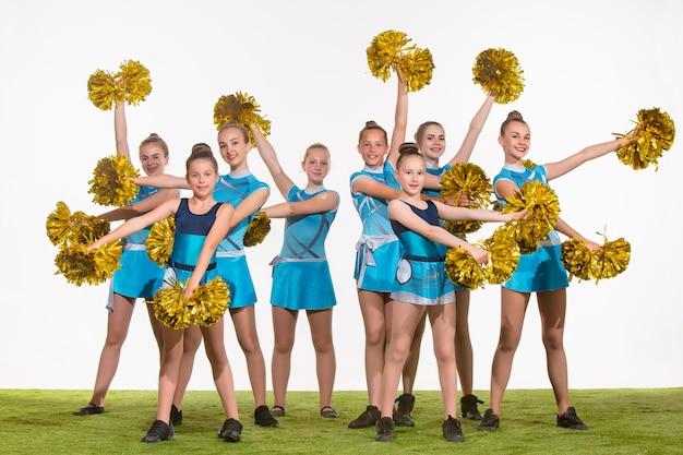 Le groupe de pom-pom girls adolescents posant au studio blanc