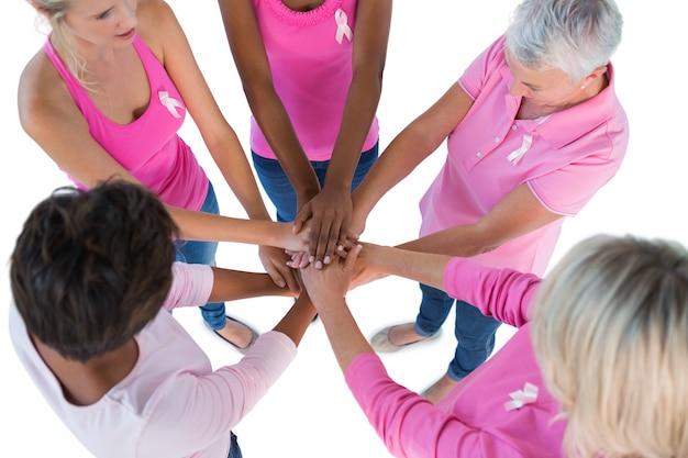 Groupe portant des roses et des rubans pour le cancer du sein avec les mains ensemble