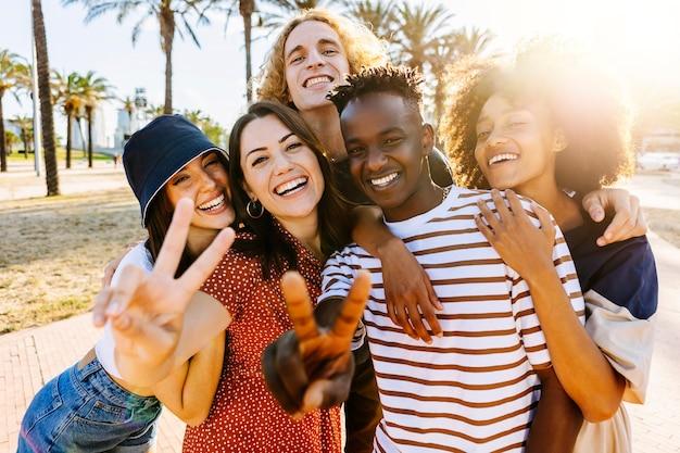 Groupe de portraits de jeunes amis multiculturels à la mode regardant la caméra en se tenant debout près des palmiers