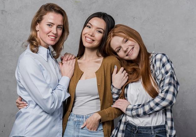 Groupe positif de femmes souriant ensemble
