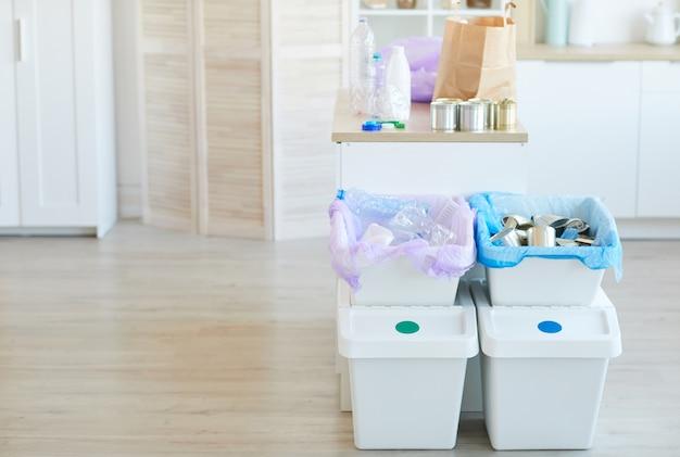 Groupe de poubelles avec différents déchets triés dans la salle domestique