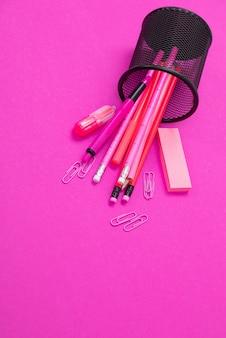 Groupe de produits de papeterie de couleur rose sont dispersés dans un bac à crayons de haut en bas sur rose isolé