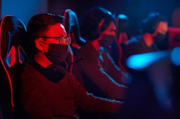 Groupe de programmeurs informatiques dans des masques de protection à l'aide d'ordinateurs dans leur travail dans un bureau sombre