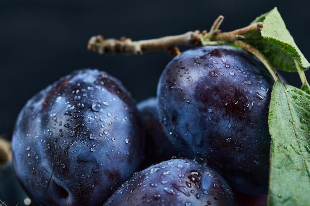 Groupe de prunes fraîches sur fond noir.