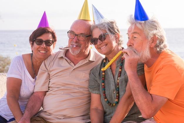 Groupe de quatre amis âgés et matures célébrant une fête ou un événement ensemble à la plage. aînés s'amusant et appréciant l'anniversaire
