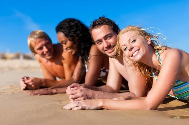 Groupe de quatre amis - hommes et femmes - sur la plage s'amusant pendant leurs vacances
