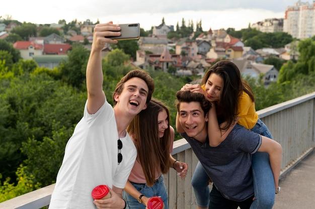 Groupe de quatre amis passant du temps ensemble à l'extérieur et prenant un selfie