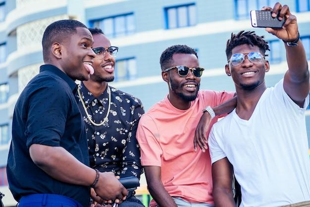 Un groupe de quatre étudiants afro-américains à la mode et cool communiquant dans la rue en regardant un smartphone prennent des photos en selfie au téléphone.