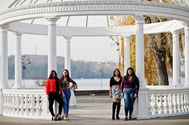 Groupe de quatre filles latino-américaines heureuses et jolies d'equateur posées dans la rue contre une arche ancienne.