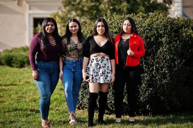 Groupe de quatre filles latino-américaines heureuses et jolies d'equateur posées dans la rue.