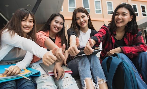 Groupe de quatre jeunes étudiantes asiatiques séduisantes assises ensemble sur le campus universitaire en plein air faisant des pouces vers le haut. concept pour l'éducation, l'amitié et la vie des étudiants.