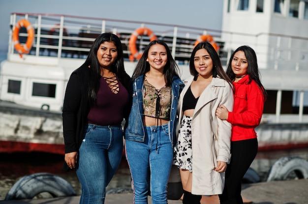 Groupe de quatre jeunes filles latino-américaines heureuses et jolies posées contre le bateau.