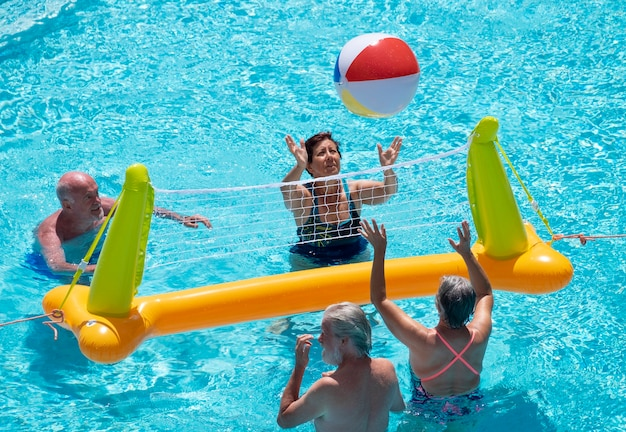 Groupe de quatre personnes âgées jouant au volley-ball dans la piscine avec filet gonflable et ballon souriant