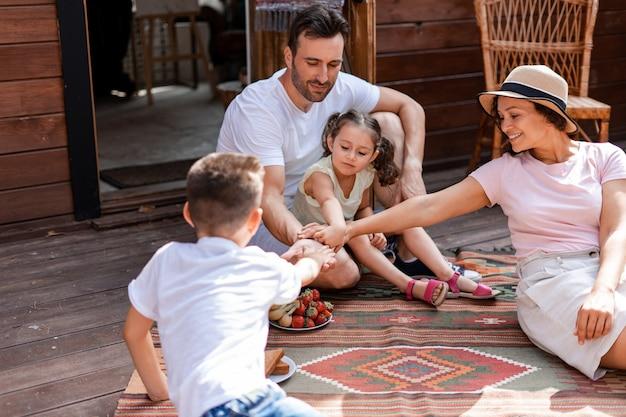 Un groupe de quatre personnes assis sur un porche en bois, se réjouissant de l'ambiance estivale, se tenant la main en équipe, une famille de quatre personnes profitant du temps ensemble