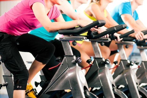 Groupe de quatre personnes tournant dans la salle de sport, exerçant leurs jambes en cardio-training