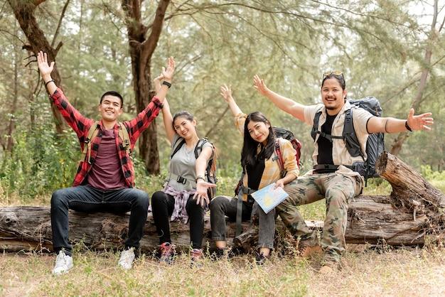 Un groupe de quatre randonneurs hommes et femmes asiatiques assis sur une bûche dans la forêt avec des expressions joyeuses.