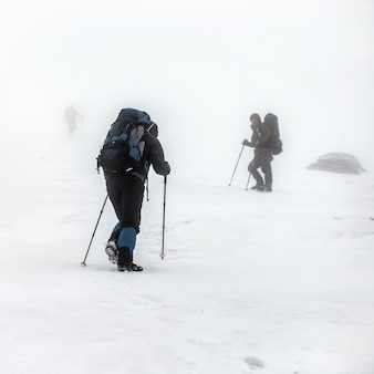 Groupe de randonnée en montagne avec sacs à dos et bâtons de randonnée ayant un voyage d'escalade difficile dans la tempête de neige hivernale