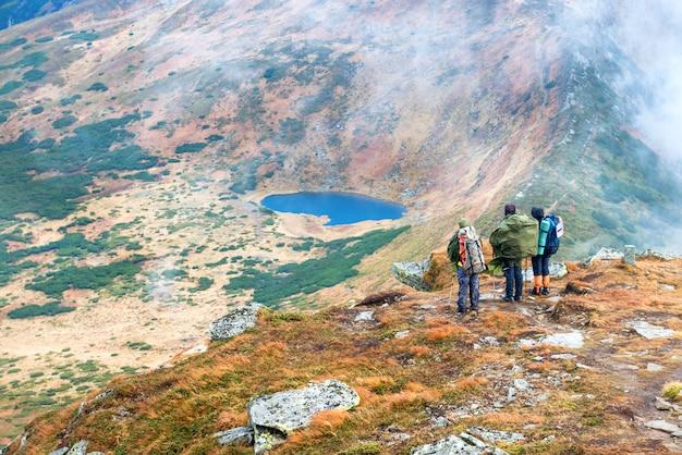 Groupe de randonneurs et d'amis dans les montagnes regardant le paysage avec le lac bleu
