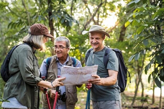 Groupe de randonneurs seniors vérifiant une carte pour la direction