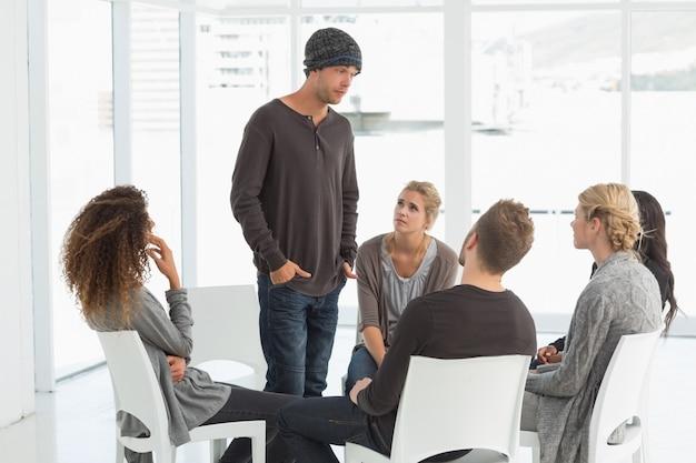 Groupe de réadaptation écoutant l'homme debout se présentant